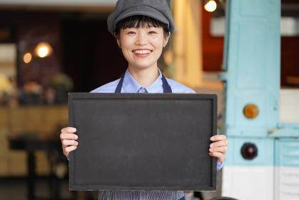 キッチンカーの前でメッセージボードを持つ女性店員