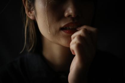 涙を流しながら爪を噛む女性
