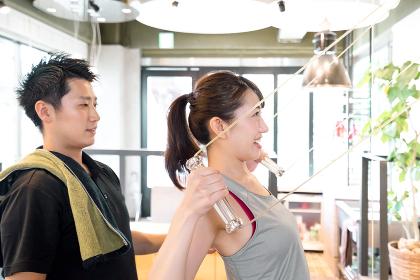 トレーナーに教わりながら広背筋をトレーニングする女性