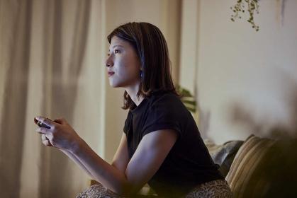 リビングでゲームをする若い日本人女性