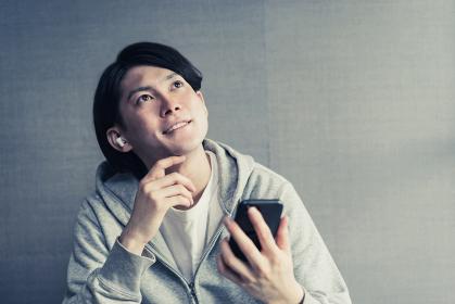 ワイヤレスイヤホンで好きな音楽を聞く若い男性