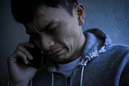 通話しながら涙を流す男性