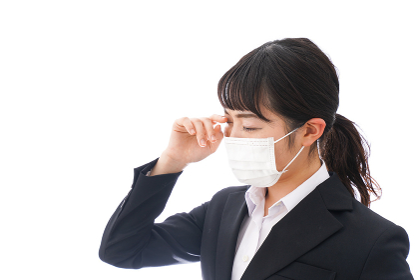花粉症・風邪・インフルエンザに苦しみマスクをする若い女性