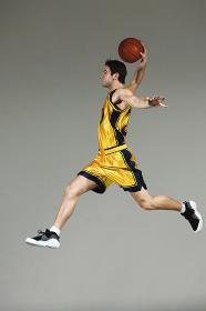 ダンクシュートをするバスケット選手の横向き