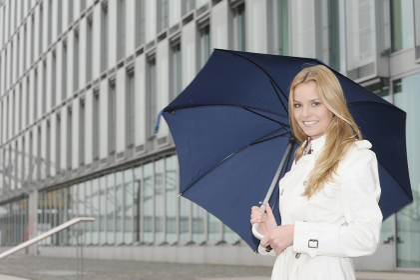 Woman carrying umbrella on city street