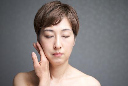 手の甲で頬を押さえる中年の日本人女性