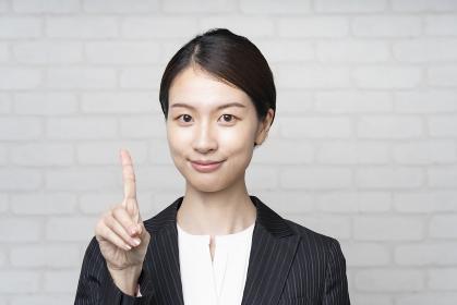 人差し指を立てるアジア人の若いビジネスウーマン