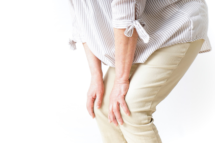 膝の痛みを感じる高齢者の女性