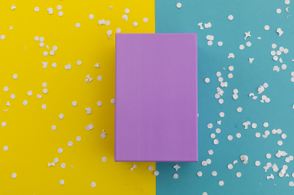 Purple gift box and white confetti on yellow and blue background. happy birthday party celebration giving receiving concept.