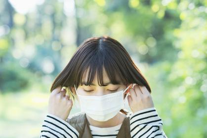 緑あふれる場所でマスクを外す若い女性