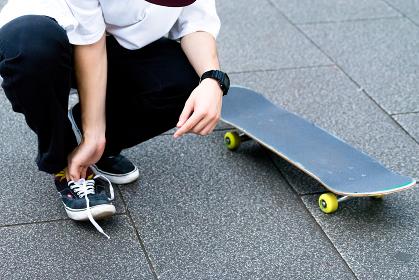 靴紐を結ぶ男性とスケートボード