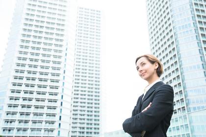 高層ビルを前に腕組みをする女性