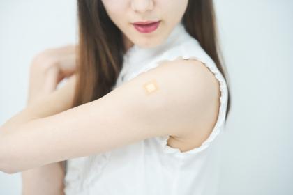 ワクチン接種のパッチが貼られた女性の腕