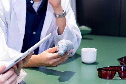 3Dプリンターで作成したカバのオブジェを持つ男性(手元)
