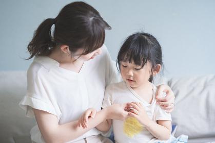 母親に体温を計測してもらう女の子