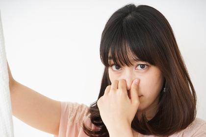 臭い洗濯物の匂いを嗅ぐ若い女性