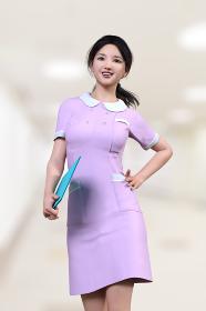 ピンクの看護服を着た日本人女性が青いファイルを片手に持ち腰に手を当て病院の廊下でポーズをとる