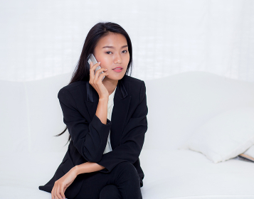 Beautiful young asian woman talking phone and smile in the livin
