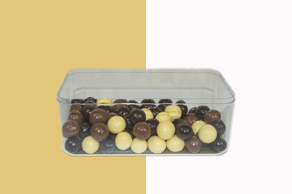 Box of chocolate balls on white and brown background
