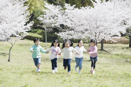 公園で手を繋いで走る5人の子供たち