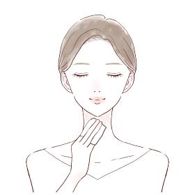 化粧水を含ませたコットンを首に塗り、肌を保湿する女性