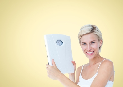Woman holding Weight scales against a yellow background