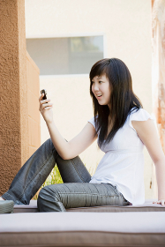 Happy teen reading text on mobile phone