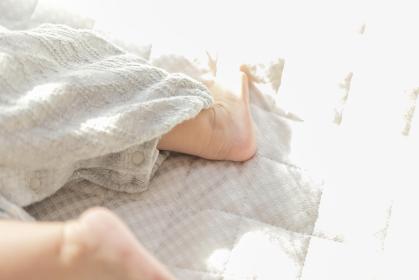 明るい部屋の中で寝転ぶ赤ちゃんの足