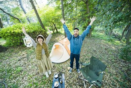 キャンプで記念写真を撮る男女