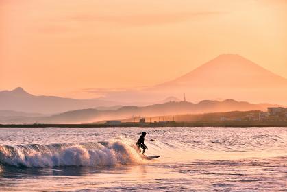夕焼けの富士山とサーファー(シルエット)