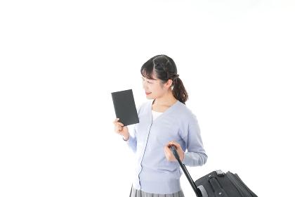 ガイドブックを持ち一人旅をする若い女性