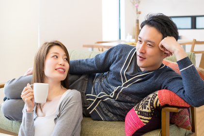会話しながら同じ画面を見るカップル(ホームシアター・テレビ・映画)