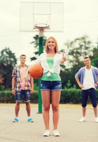 group of smiling teenagers playing basketball