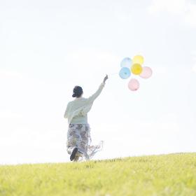 風船を持ち草原を走る女性の後姿