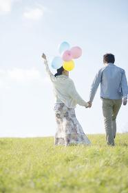 風船を持ち草原を歩くカップルの後姿