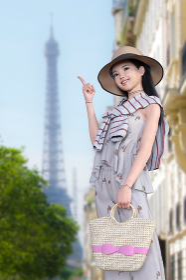 花柄のオールインワンを着た笑顔の女の子が麦わら帽子をかぶり大きな電波塔を指差す