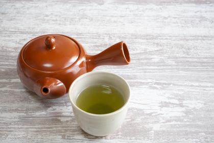 緑茶の入った湯呑みと茶色の急須