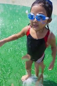 水飛沫を浴びる水着姿の女の子