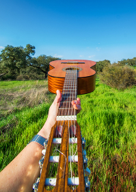 Hand Holding A Spanish Guitar With Nature Background.Music And Nature