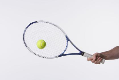 ラケットでテニスボールを打つ瞬間
