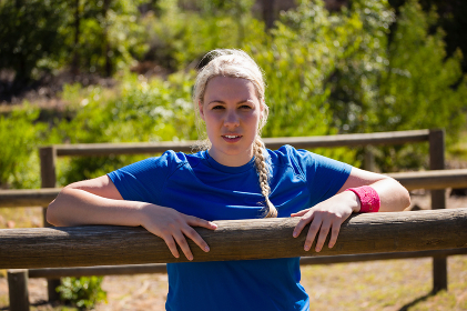 Fit woman leaning on hurdles during obstacle course training in the boot camp
