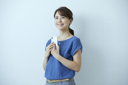 スマートフォンを持つ笑顔の日本人女性