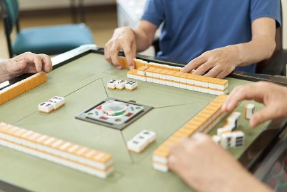介護施設のレクリエーションルームで麻雀をする高齢者