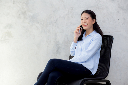 Beautiful young asian woman talking smart mobile phone and smile
