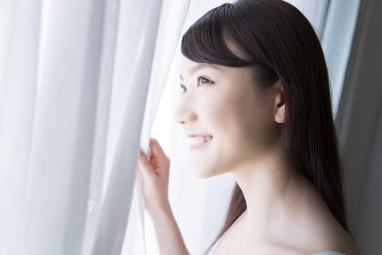 カーテンを開けて微笑む女性