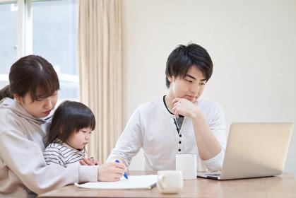 テレワークをするアジア人男性と子育てをする女性