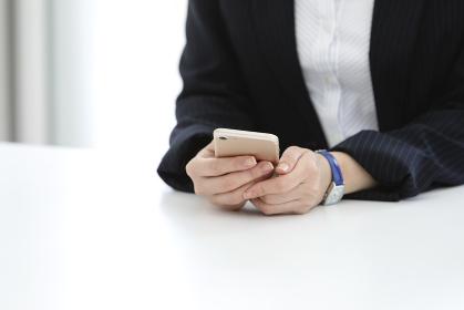 スマートフォンを持つビジネスウーマンの手元