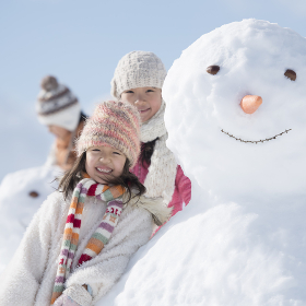 雪だるまの周りで微笑む小学生