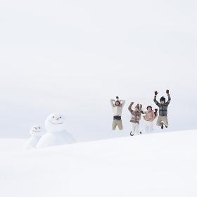 雪原でジャンプをする大学生