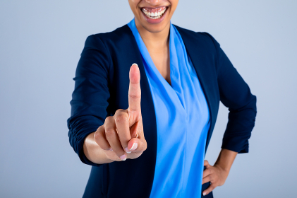 Mid section of businesswoman smiling while touching invisible screen against grey background. business, professionalism and technology concept